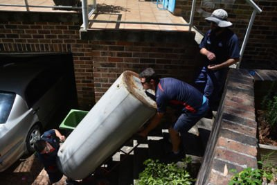 Technicians disposing of a old rusty water heater